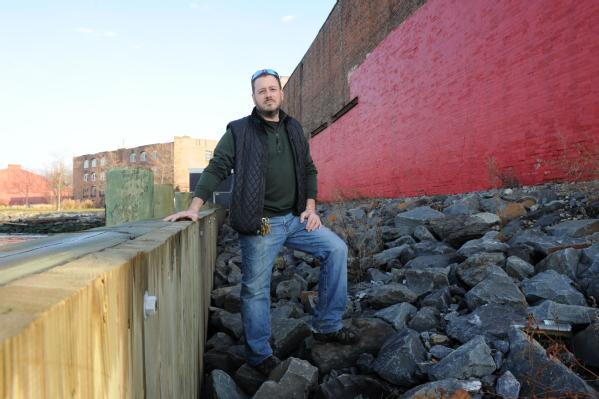 Brooklyn, N.Y., Dec. 4, 2012 -- Brian Robbins, owner of Cornell Paper and Box Company, Inc., stands next to his business which abuts Upper New York Bay. Robbins took the initiative to mitigate his property by building a bulk head wall to protect his property from storm surge. Although Robbins building was flooded due to Hurricane Sandy, he said that without the mitigation steps, he would have lost his whole building.