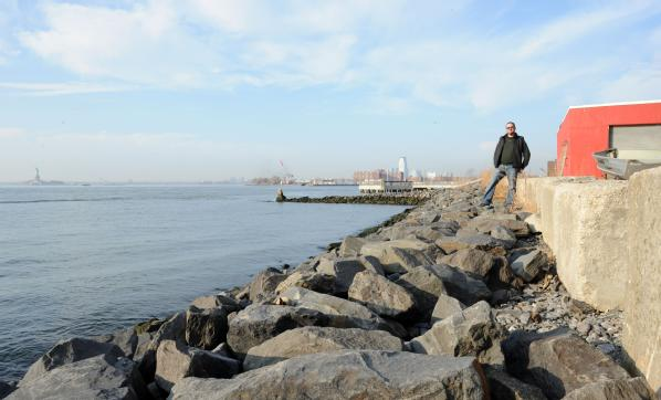 Brooklyn, N.Y., Dec. 4, 2012 -- Brian Robbins, owner of Cornell Paper and Box Company, Inc., stands next to his business which abuts Upper New York Bay. Robbins took the initiative to mitigate his property by building a stone wall to protect his property from storm surge. Although Robbins building was flooded due to Hurricane Sandy, he said that without the mitigation steps, he would have lost his whole building.