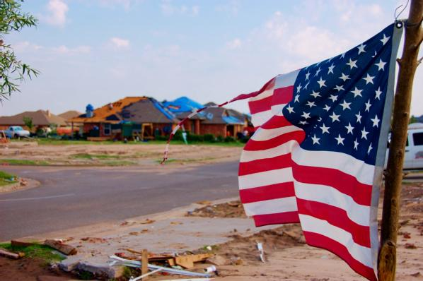 Moore, Okla., July 29, 2013 -- The American flag stands as a sign of strength in the foreground of the devastation left in the wake of the May 20th EF-5 tornado.